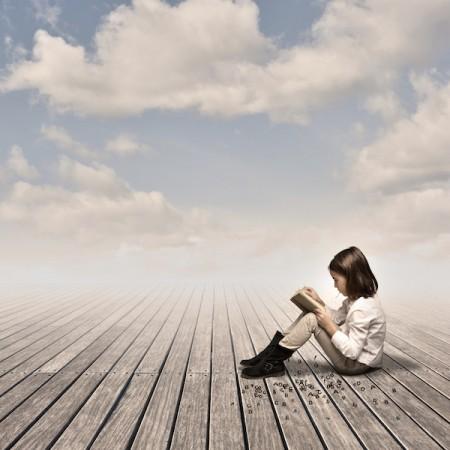 little girl reading a book on a wharf